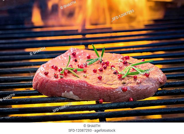 A fresh steak with pepper and rosemery on a grill rack with fire