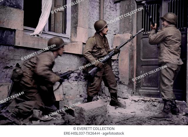 Infantrymen batter down the door of a house where German snipers were holding out. Stavelot, Belgium, during the Battle of the Bulge. Dec. 19-20, 1944
