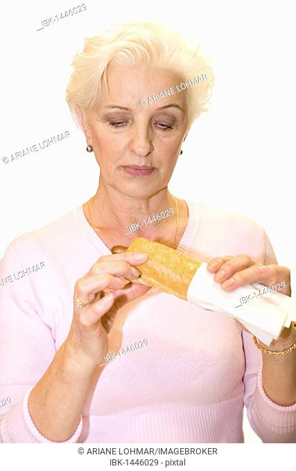 A woman eyeing a sausage in a baguette suspiciously