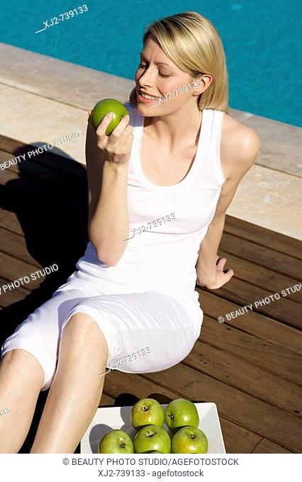 Woman outdoors eating apples
