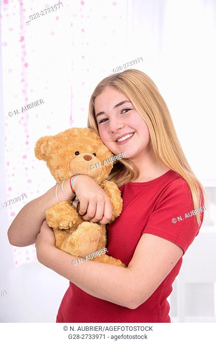 young school girl, 15 year old, in red, with a broad smile, holding her teddy bear and cuddling it