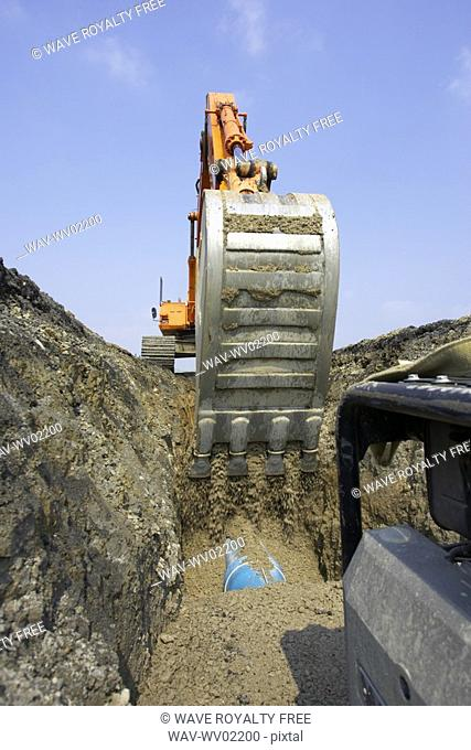Excavator filling in section of drainage pipe with dirt, Canada, Ontario, Hamilton Composting Facility