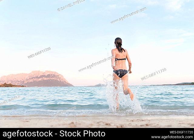 Back view of woman in bikini running into the sea, Sardinia, Italy