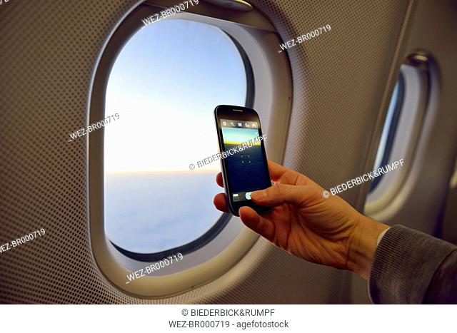 Man taking picture with smartphone at airplane window