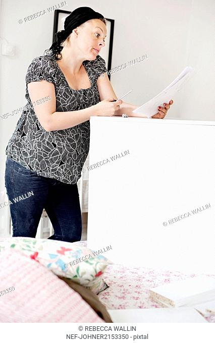 Pregnant woman assembling furniture