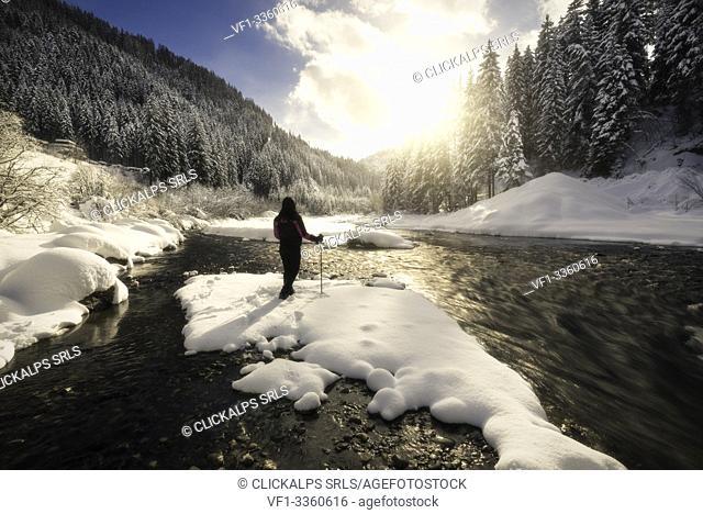 Hiker admire the sun on Gadera river in a winter day, badia valley, Bolzano province, South Tyrol, Trentino Alto Adige, Italy