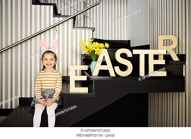 Portrait of smiling girl with bunny ears sitting on stairs next to word 'Easter'