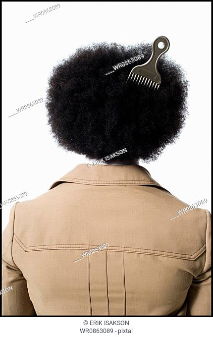 Man with an afro in beige suit with hair pick in hair