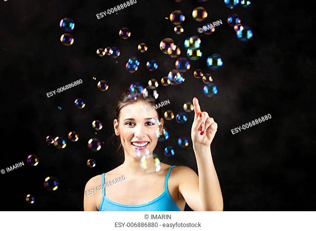 Happy girl and soap bubbles on the black background