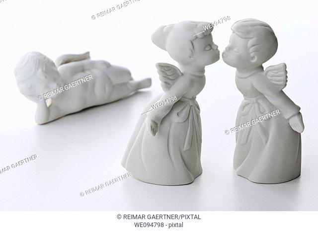 White porcelain boy and girl angels kissing with a third angel watching in the background