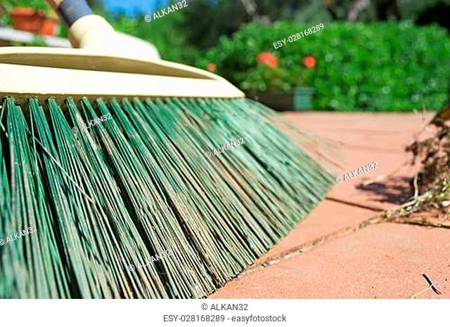 closeup of a green broom on a red floor