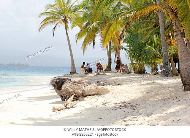 Group of Kuna Indians sitting in the palm grove on the sandy beach of San Blas Islands, Panama, Central America
