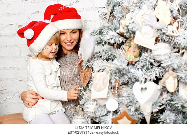 The pretty girl with mum are decorating a Christmas tree in the house. Happy family