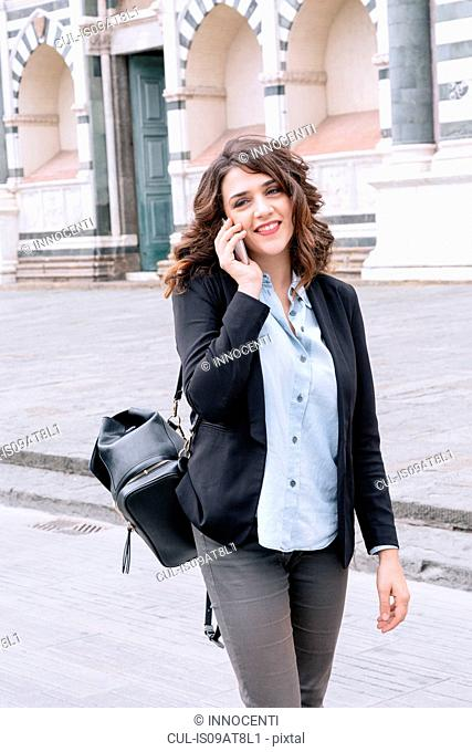 Young woman talking on cellular phone looking away smiling, Piazza Santa Maria Novella, Florence, Tuscany, Italy