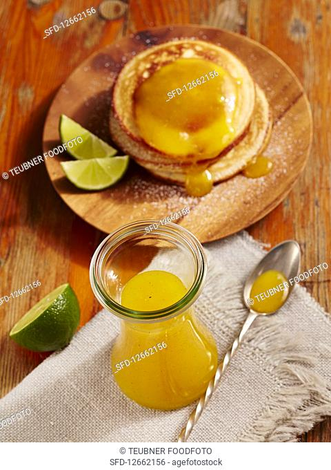Homemade mango syrup with pancakes and limes