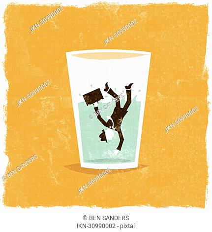 Businessman falling in glass of water