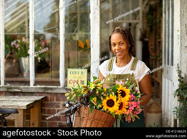 Portrait female florist with flowers in bike basket outside shop