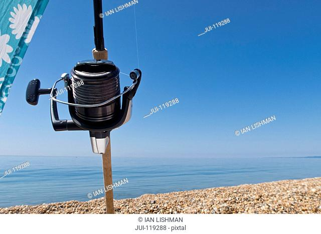 Close-up of fishing reel and rod on pebble beach with ocean and blue sky background