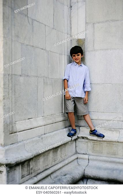 portrait of 10 year old child with stone wall background of a cathedral