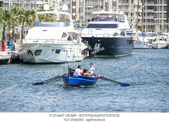 Rowing boat in the harbour at Santa Pola in Alicante Spain with large Yachts moared in the background