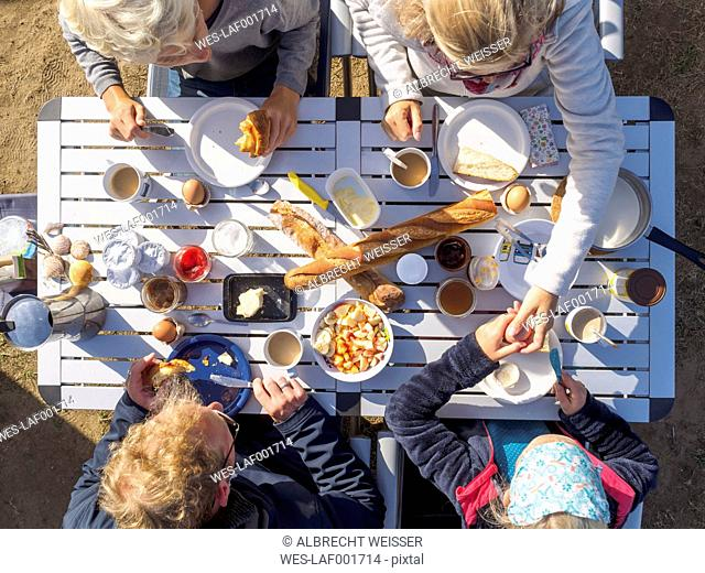 Family sitting on table, breakfast