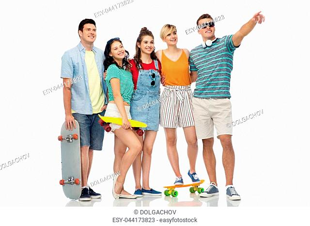 friendship, extreme sport and people concept - happy friends with skateboards over white background pointing finger to something