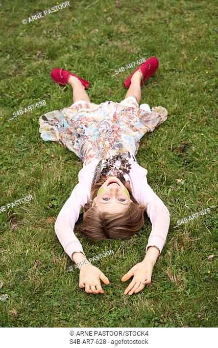 Girl is lying on a meadow