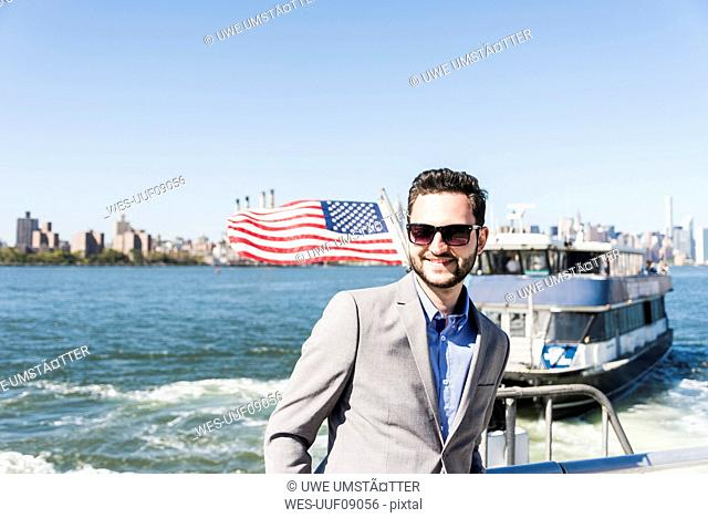 USA, New York City, smiling businessman on ferry on East River