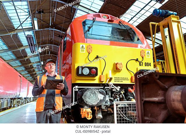 Engineer inspecting locomotive in train engineering factory