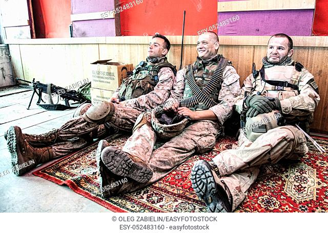 United States marines in camouflage uniform and ammunition sitting on floor at combat outpost or temporary base on mission, talking in relaxing atmosphere