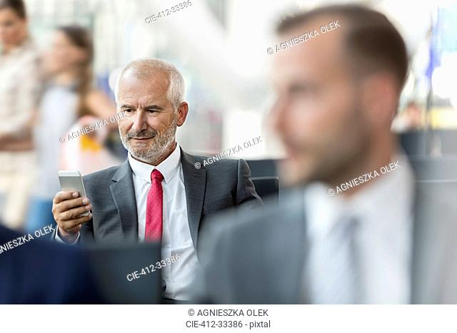 Businessman texting with cell phone in airport departure area