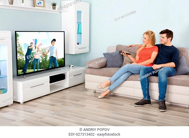 Young Couple Sitting On Sofa And Enjoying Watching Television