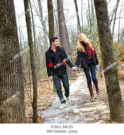 A couple walking hand in hand through a woodland in winter