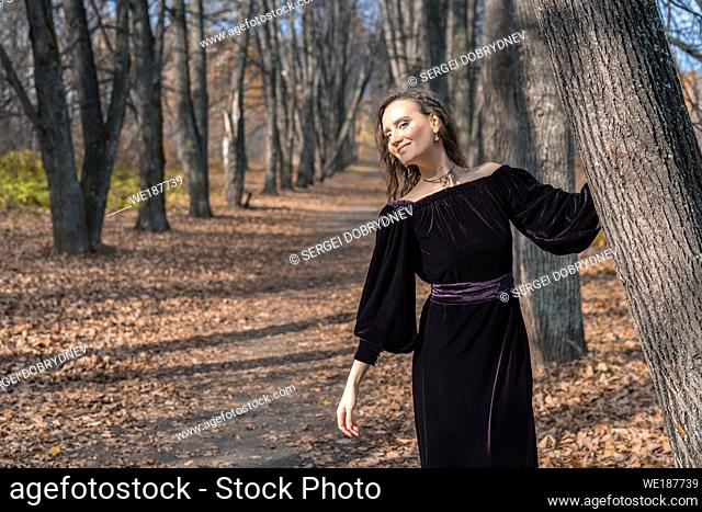 Girl in a dark dress on a linden alley in an autumn day