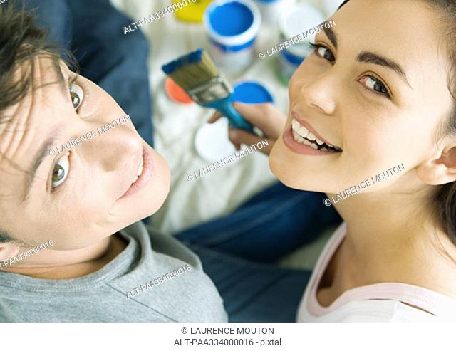 Couple with paint materials, smiling at camera