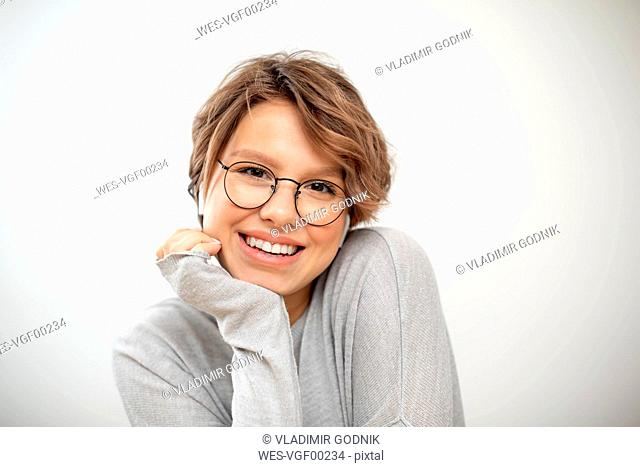 Portrait of laughing young woman with wireless earphones and glasses