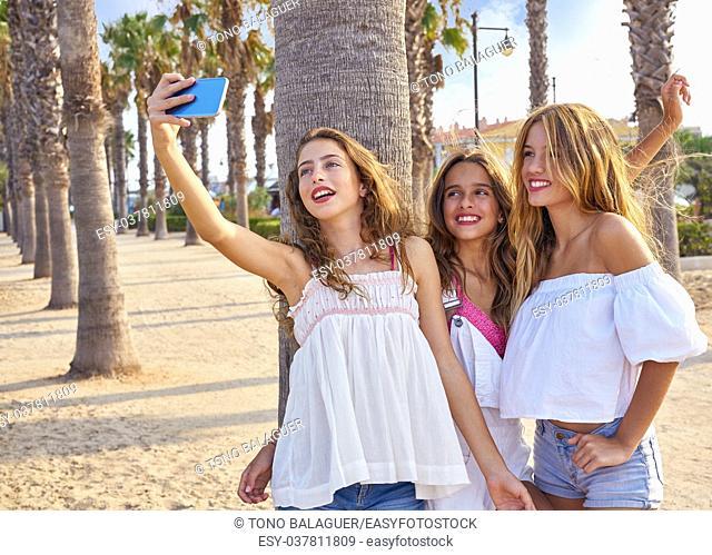 Teen best friends girls group shooting selfie photo smartphone in palm trees beach