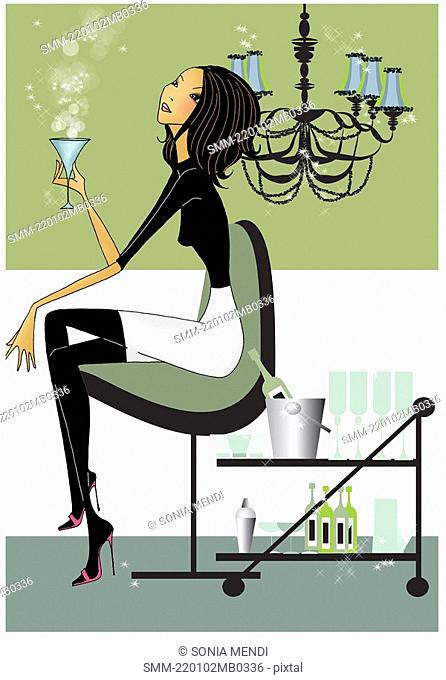 Woman sitting in a modern chair with a cocktail