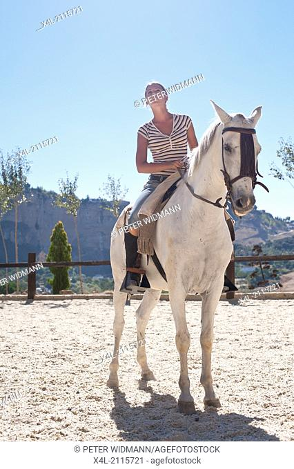 young, pretty woman on summer holiday in Ronda, horse back riding on white Andalusian horse, Spain, Andalusia, Ronda (model-released)