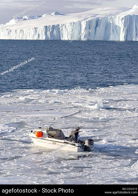 Fisherman fishing in the fjord. Winter at the Ilulissat Icefjord, located in the Disko Bay in West Greenland, the Icefjord is part of the UNESCO world heritage