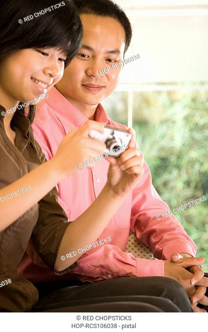 Young woman holding a digital camera with a young man sitting beside her