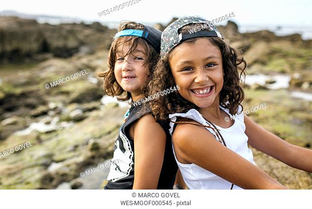 Spain, Gijon, portrait of smiling little girl and her friend sitting back to back at rocky coast