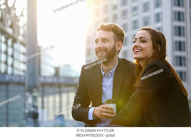 Smiling young businesswoman and businessman outdoors