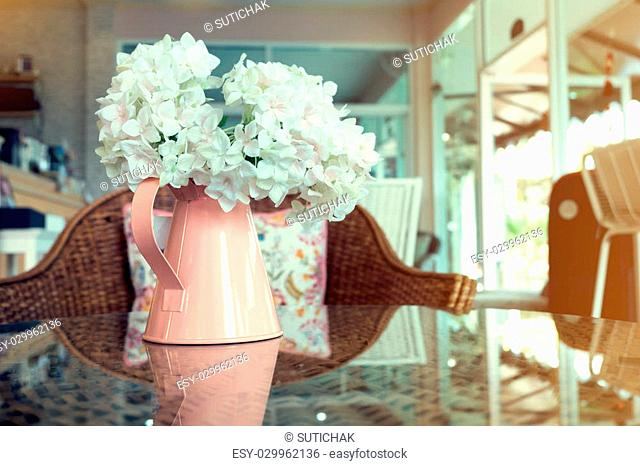 white plastic flowers in pink flower vase on the rattan weave table decorated interior in cafe