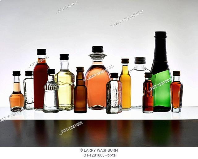 A grouping of various miniature bottles of alcohol without labels, back lit