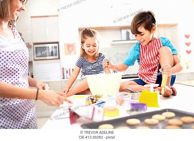 Mother and children baking cookies in kitchen