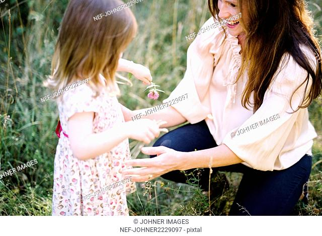 Mother with daughter on meadow