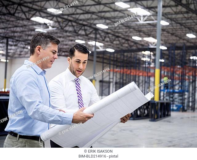 Caucasian architects reading blueprints in warehouse