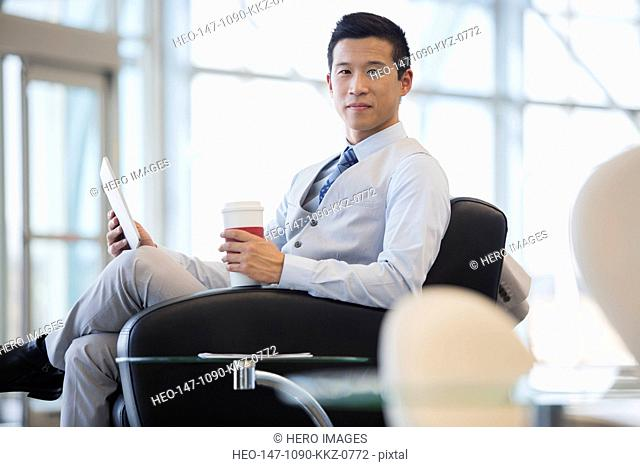 Portrait of businessman with digital tablet and coffee
