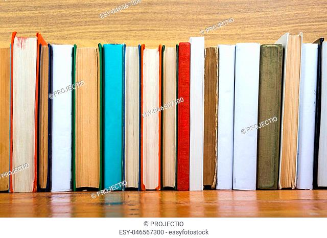 Colorful composition with vintage old hardback books, diary on wooden deck table and wood background. Books stacking. Back to school. Copy Space